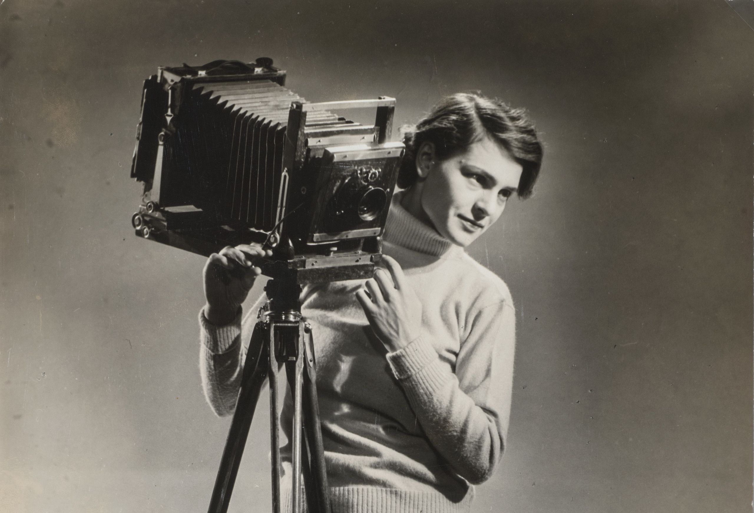 A black-and-white photograph of a light-skinned adult woman standing next to a vintage camera mounted on legs.