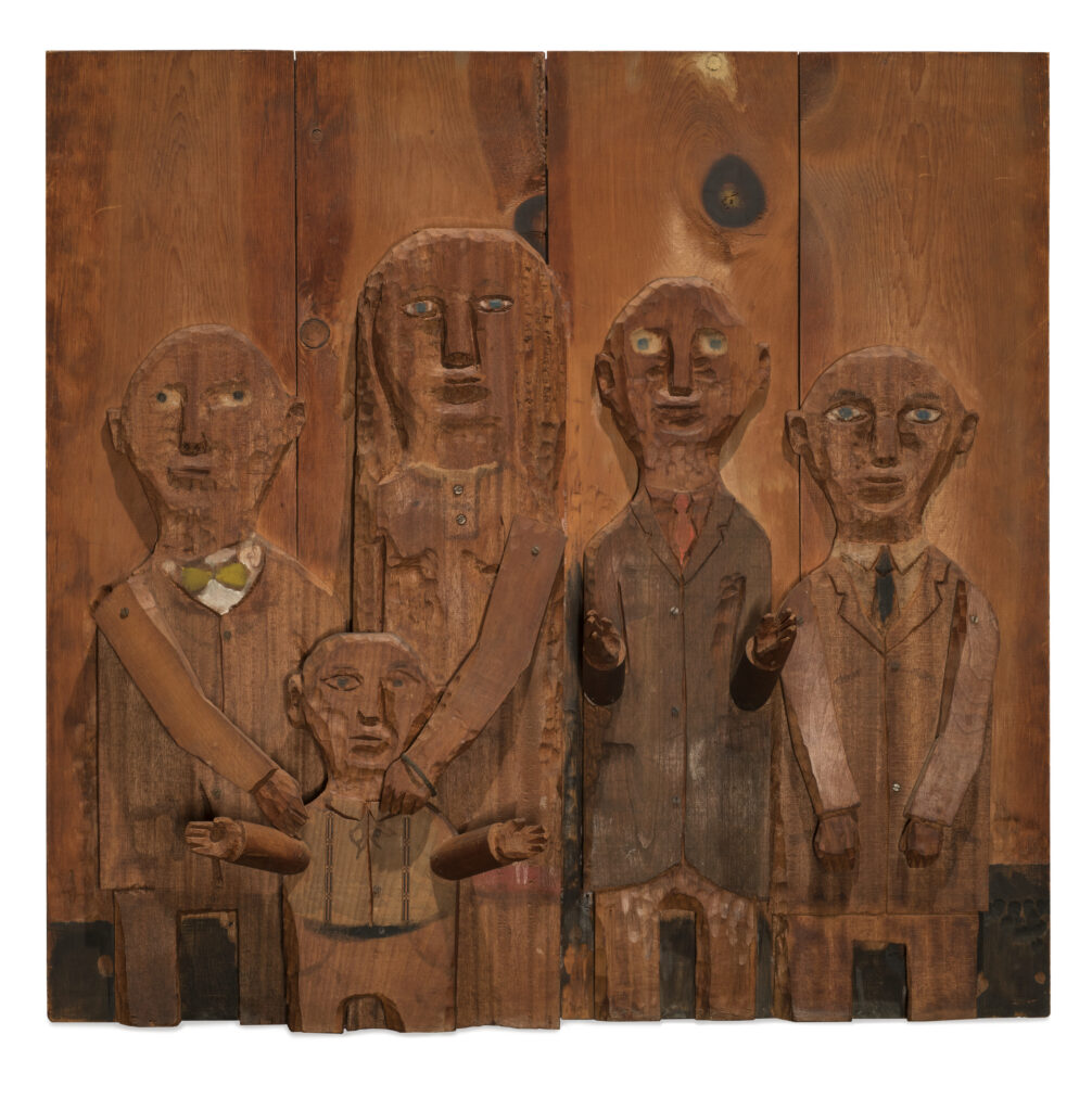 A wooden relief sculpture of four adults and one child. The two figures on the left put their hands on the shoulders of the child in front of them. The arms and hands of all figures are three dimensional and protrude from the work.