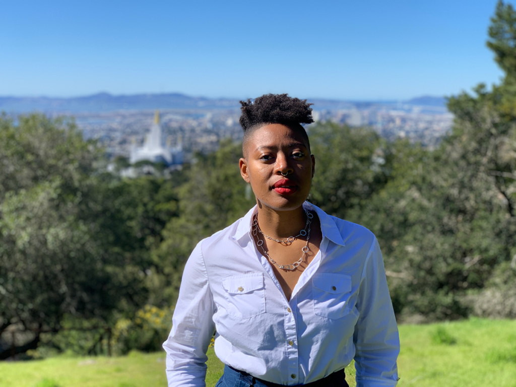 A headshot of Dr. Ayana Flewellen, who stands in a white blouse with a silver necklace; the blurry background is a landscape of lush green trees and mountains in the far background.
