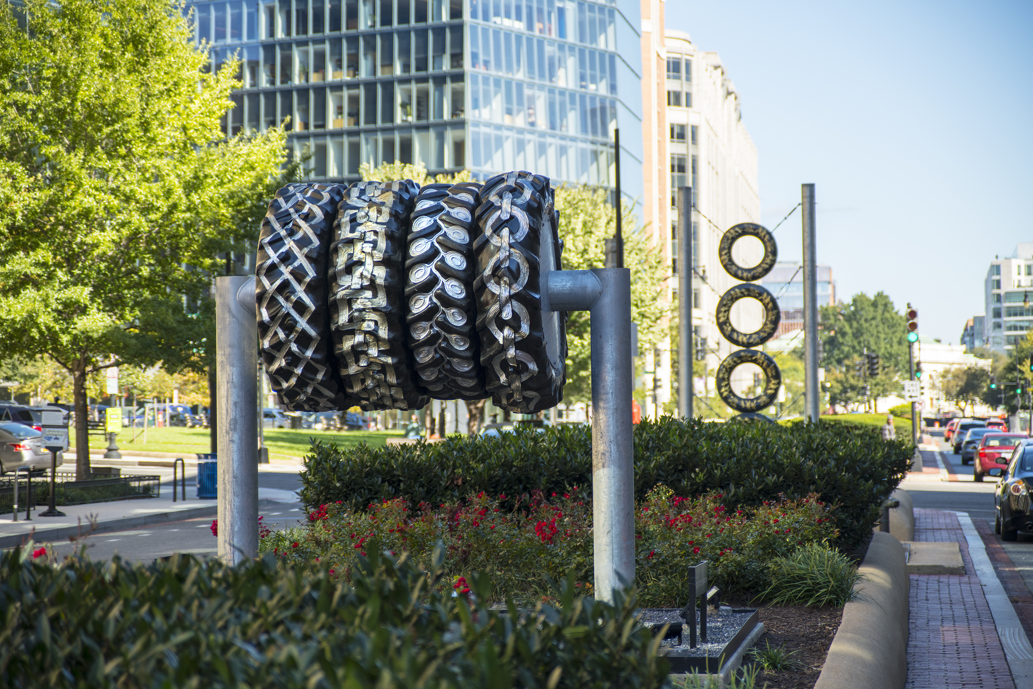 "An installation shot of Bestabee Romero's ""Signals of a Long Road Together"" installation on New York Avenue in Washington, D.C. The tire sculptures are suspended in the median of the road--one with four tires horizontally placed close together; another in the background with four tires placed on top of one another vertically."