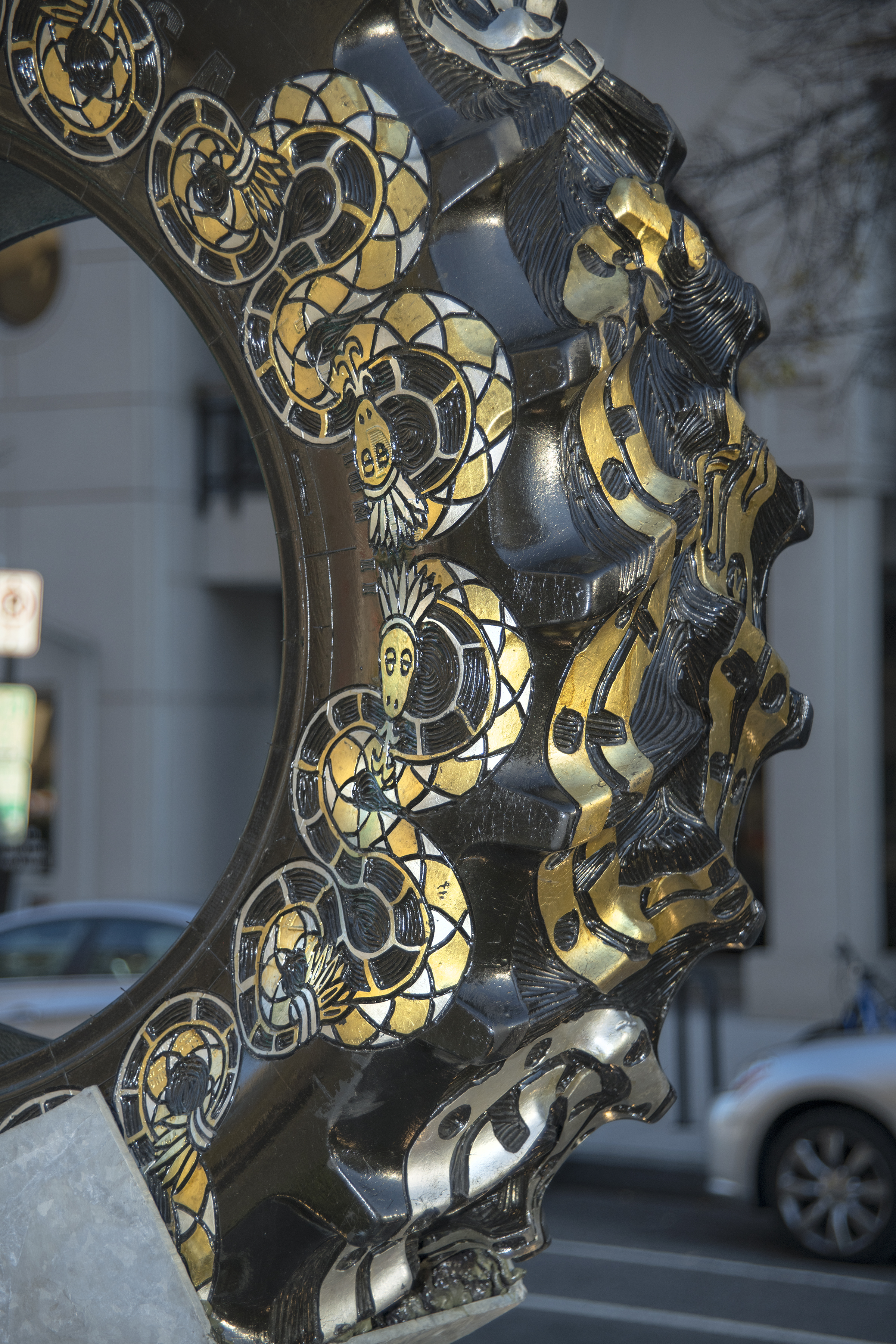 "Detail of Bestabee Romero's ""Signals of a Long Road Together"" installation on New York Avenue in Washington, D.C; this tire shows a snake carved into the tire treads and face, it coils around the full tire, the snake is painted gold and silver."