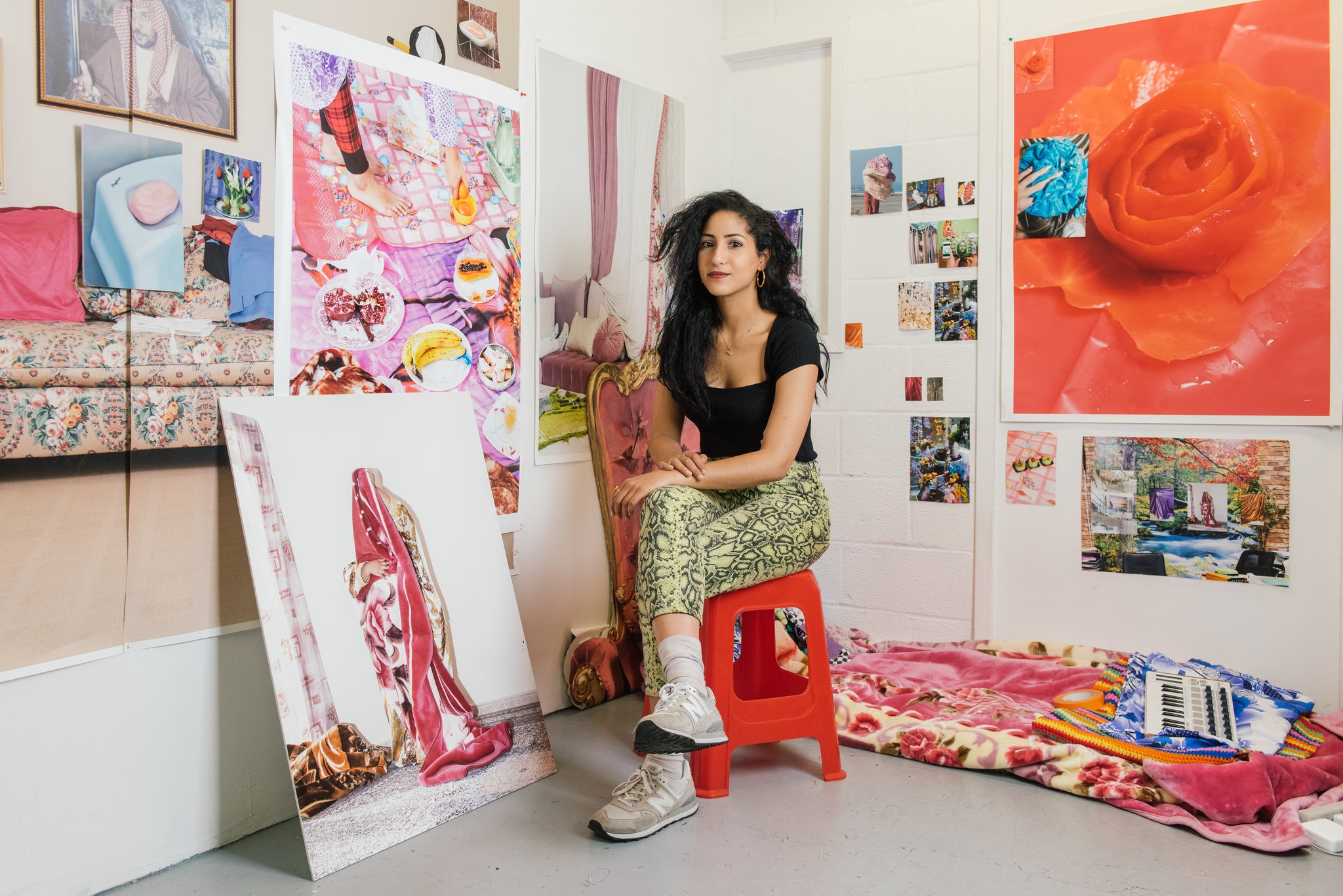 Artist Farah Al Qasimi sits in her studio in Williamsburg, Brooklyn, surrounded by her photographs from her home country, the United Arab Emirates. The photos are vibrant and colorful.