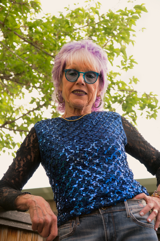 A portrait of Judy Chicago in 2019; the artist is wearing a blue sequined shirt and jeans, purple short hair, and has her hands on her hips, the background is a tree.