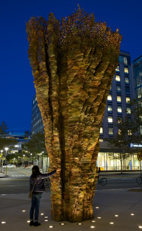 Ursula von Rydingsvard's SCIENTIA stands outside of a MIT building at twilight at 25-feet high; Its soaring bowl form features variegated coloring and a lace-like perforated segment at the top. A student places her hand on the sculpture.