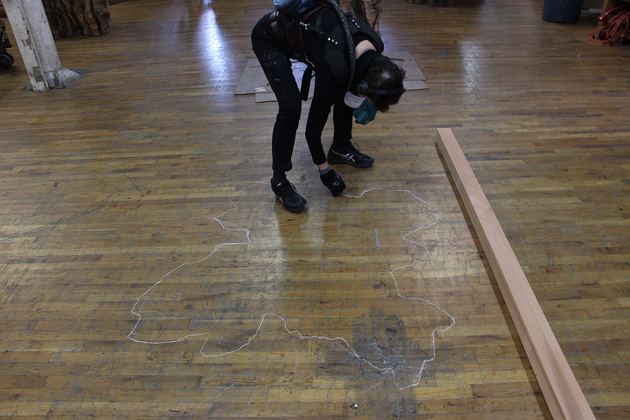 Ursula von Rydingsvard drawing on studio floor with chalk to begin a sculpture