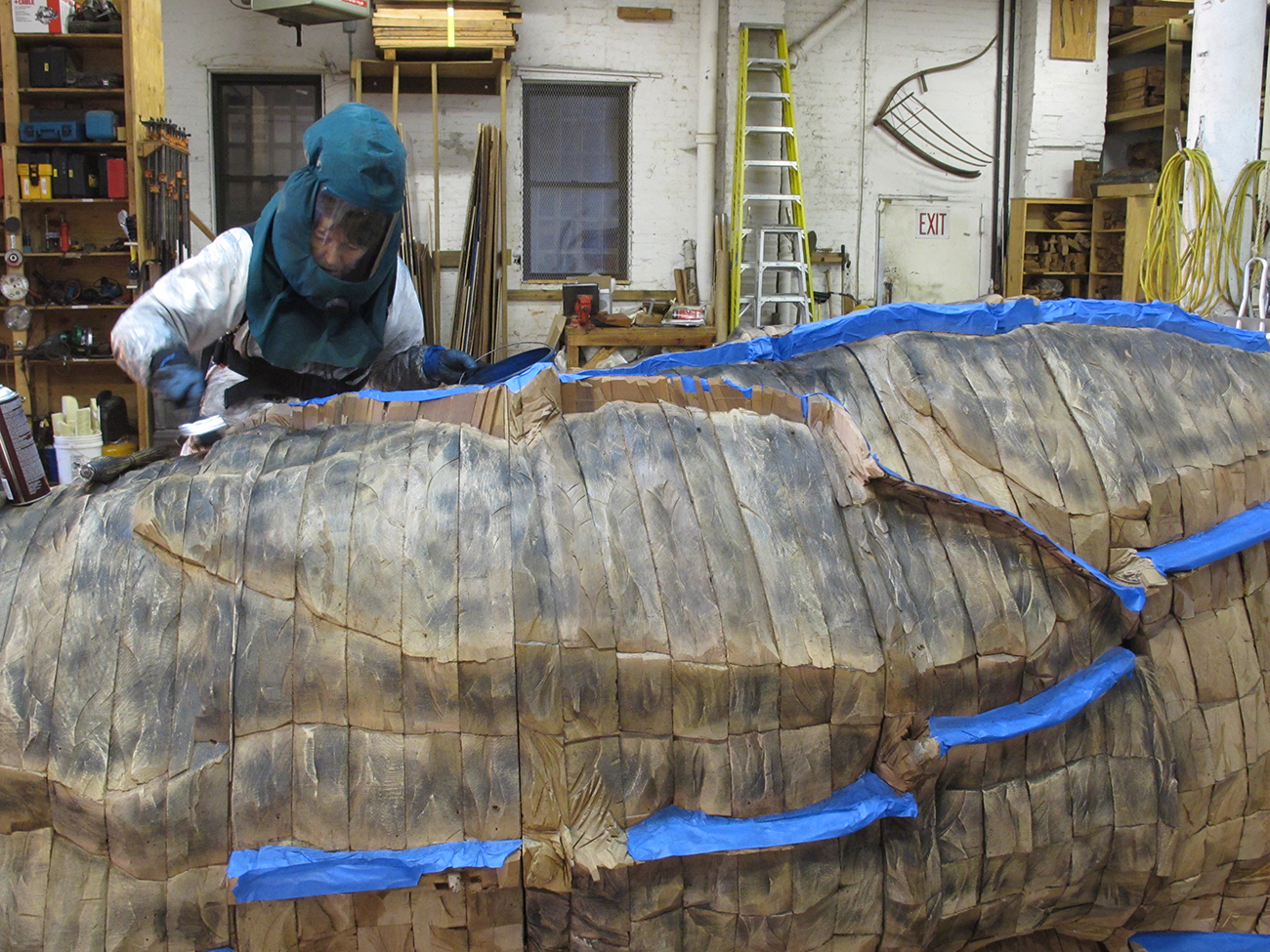 Ursula von Rydingsvard applying graphite to OCEAN VOICES, 2012. The artist wears a full protective suit.