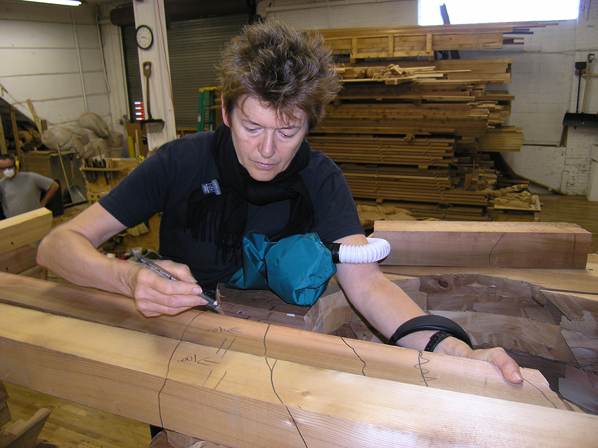 Ursula von Rydingsvard marking cedar beams with a black marker in her studio