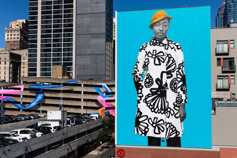 Amy Sherald's new mural in Philadelphia, depicting local Najee Spencer-Young wearing a white coat with black flowers, a yellow hat, on a bright blue background; the figure is painted in Sherald's signature grey-scale skin tone.
