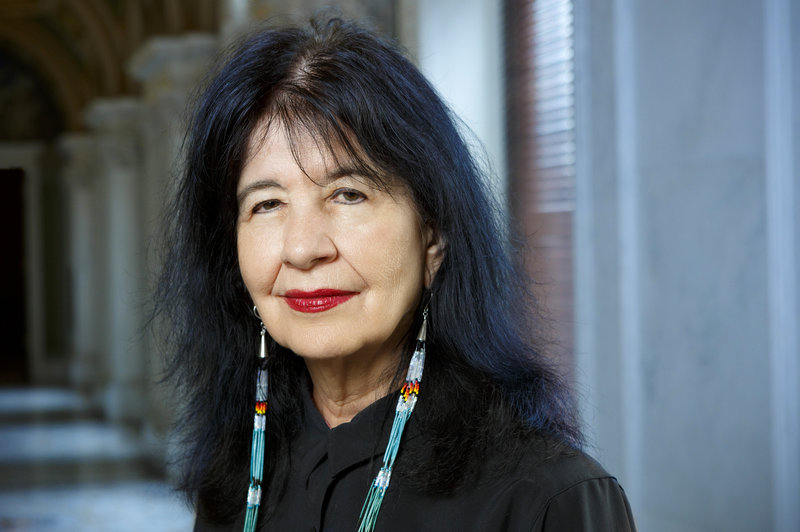 A headshot of Joy Harjo for the Library of Congress; the writer wears her black hair parted in the middle with some wispy bangs, a slight smile with red lipstick, and long intricately beaded earrings.