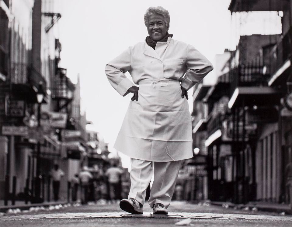 A portrait of Leah Chase from Brian Lanker's 1988 photo series I Dream a World, in which she stands smiling in her chef coat and apron in the middle of a French Quarter street with her hands posed on her hips. The shot is taken from close to ground level.