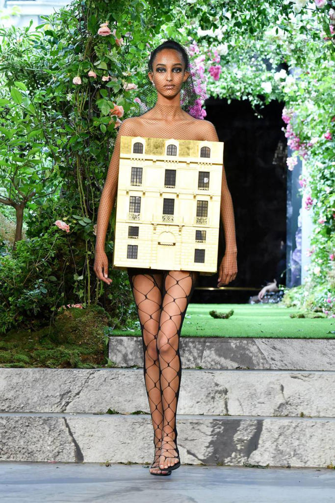 A medium dark-skinned model walks the Dior runway in a wearable golden doll house; the background in lush greenery.