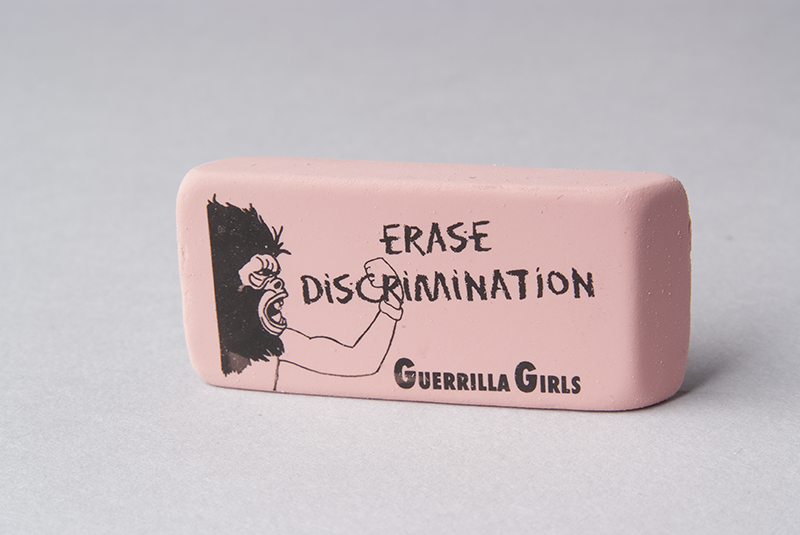 "A typical pink eraser by the Guerrilla Girls that says ""Erase Discrimination"" with their logo and name on it."