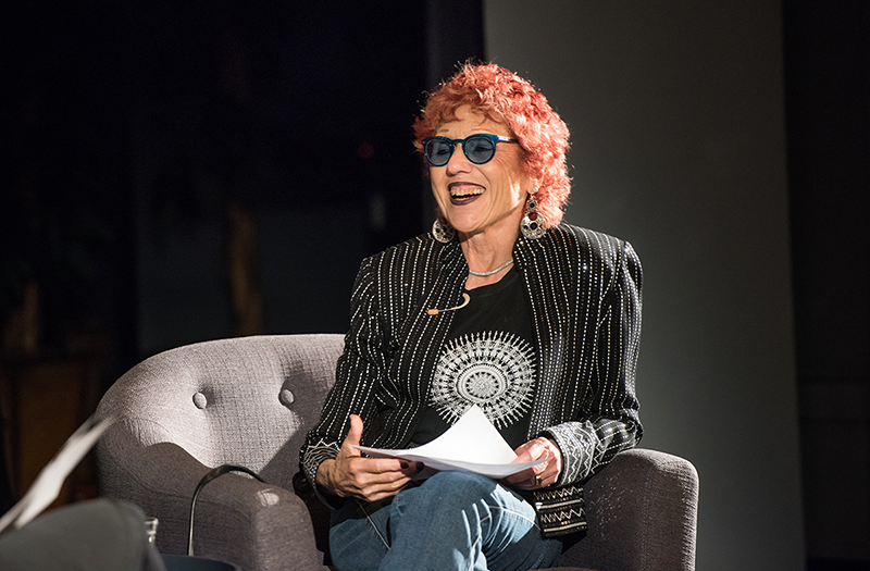 Judy Chicago sits in a grey chair on NMWA's performance hall stage, smiling and holding a piece of paper as she engages in conversation with Alison Gass (not pictured), her interviewer.
