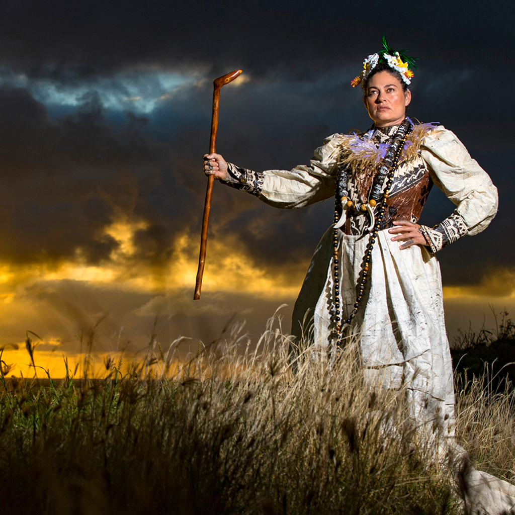 A Hawaiian woman wearing indigenous dress, necklaces, and a flower crown stands with one hand on her hip and another held out holding a polished wooden stick in a wheat grass field; behind her the sky is golden and also a moody grey filled with storm clouds.