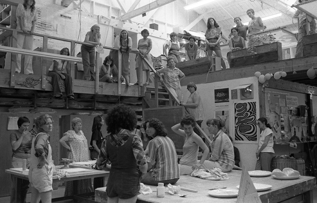 In this black and white photo, Judy Chicago addresses a gathering of volunteers in the Dinner Party studio, ca. 1978.