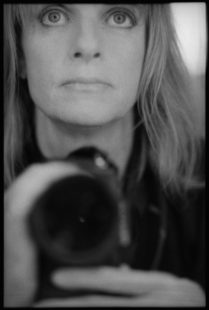 A self portrait by Linda McCartney: she looks into a mirror staring slightly upward and her camera is in the foreground and blurry.