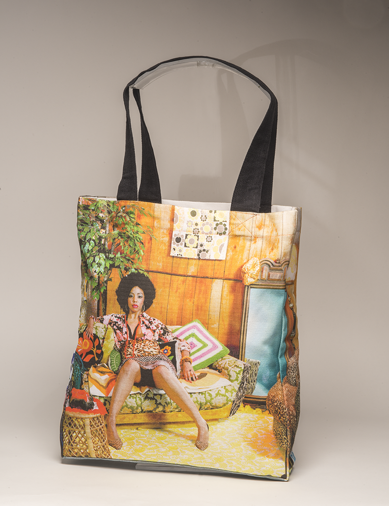 A tote bag featuring a photograph by Mickalene Thomas of a beautiful black women reclined on a couch wearing a 1970s inspired outfit, in a 1970s-esque room