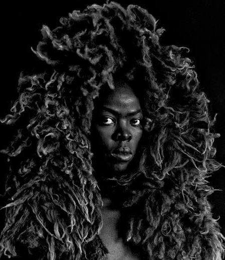 A black and white portrait photo of a black women wearing a large lion-esque headpiece and looking at the camera, with an intense side gaze.