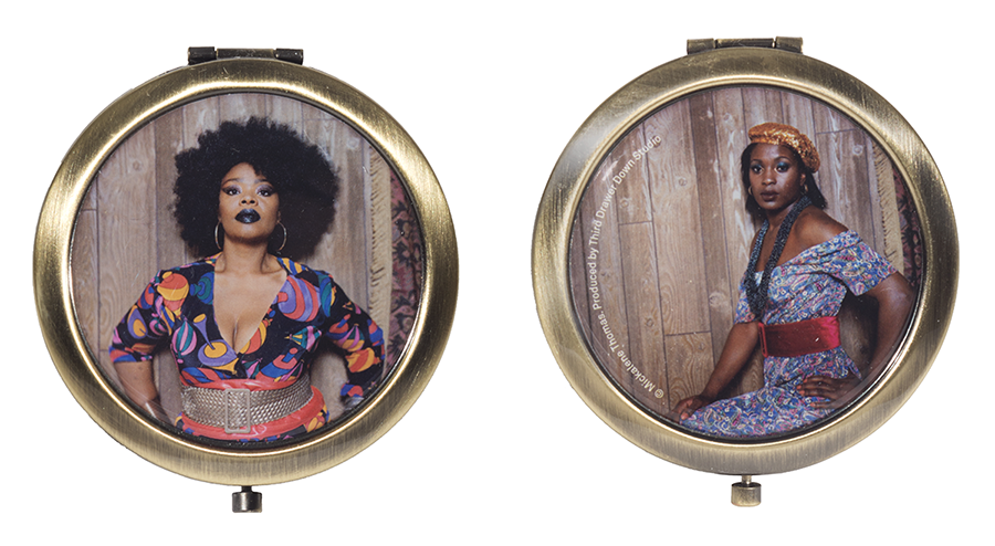 A front and back view of a pocket mirror that contain two photos of beautiful black women posed. They wear colorful dresses with wide belts. The woman on the front has an Afro, black lipstick, and hoop earrings. The woman on the back wears a long thick necklace and gold beret-fashion hat.