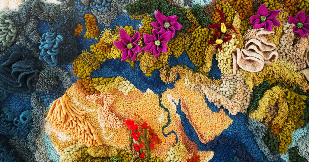 A detail shot of Vanessa Barragão's botanical tapestry which depicts the world via thread and yarn; this particular section includes the top of Africa, a bit of the Middle East, and southern Europe represented in vivid yellows with some flowers and many different stitches.
