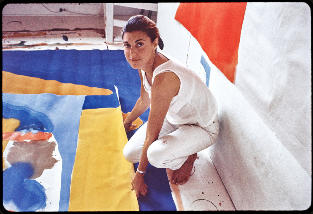 Helen Frankenthaler in her Provincetown studio; the artist wears all white and crouches before a large canvas on the floor as she looks up at the camera with a slight smile.