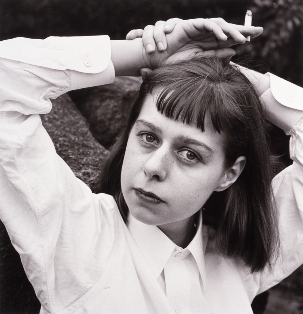 Louise Dahl-Wolfe's black and white portrait of Carson McCullers, who poses in a white oxford shirt with her hands above her head, the left clasping a cigarette.