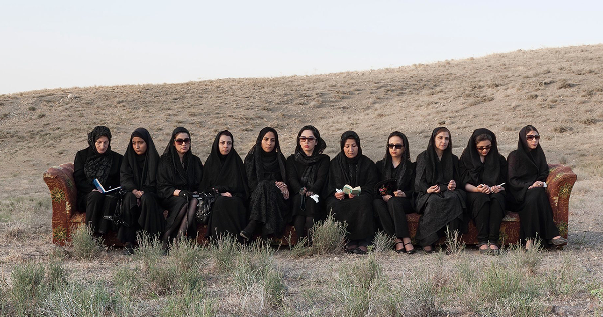 Eleven Irianian women sit on a long floral couch in the middle of the desert wearing all black and with their heads covered in hijab; their faces are drawn, several wear sunglasses, and a few are reading from books held in their hands.
