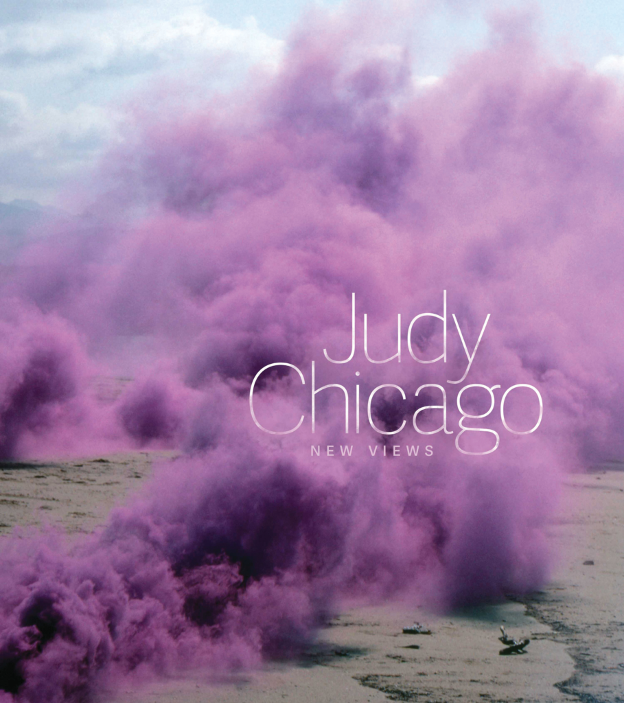 """Cover image of """"Judy Chicago: New Views""""; the book's title is placed in thin white type over a picture of purple smoke clouds billowing over sand."""