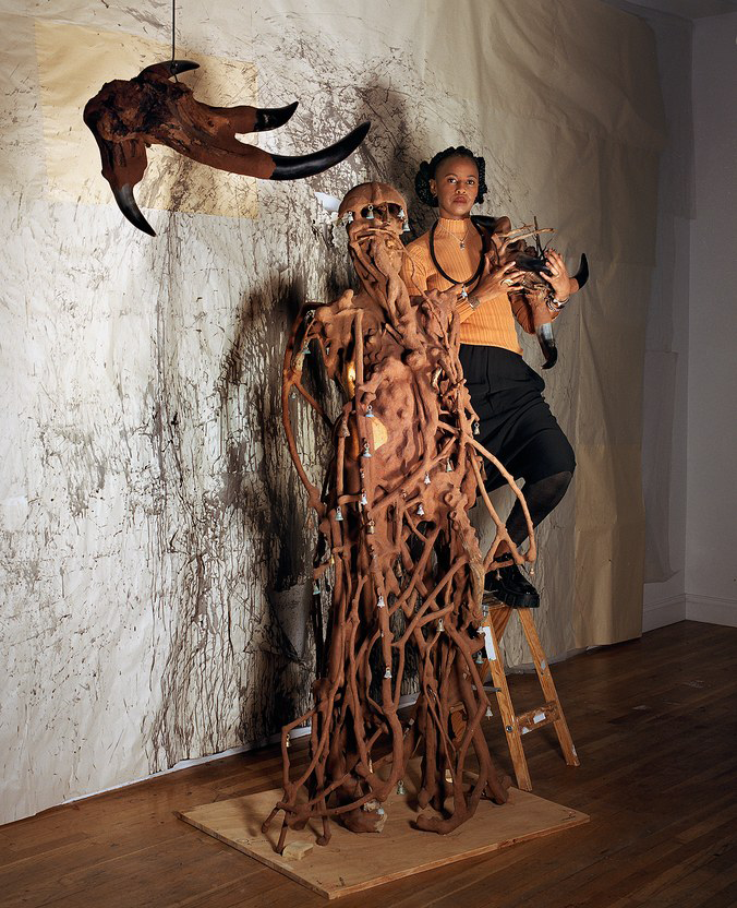 Wangechi Mutu stands atop a ladder in her Brooklyn studio, next to a 7-foot tall sculpture, part African queen, part cyborg, which will be installed in one of the exterior niches of the Metropolitan Museum of Art.