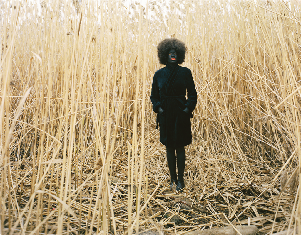 Xaviera Simmons (b. 1974) staged herself among a towering thicket of yellow reeds in her photograph One Day and Back Then (Standing) (2007). Simmons wears a black trench coat, black tights and boots, black face makeup, and bright red lipstick—a presentation that starkly juxtaposes her form against the landscape.