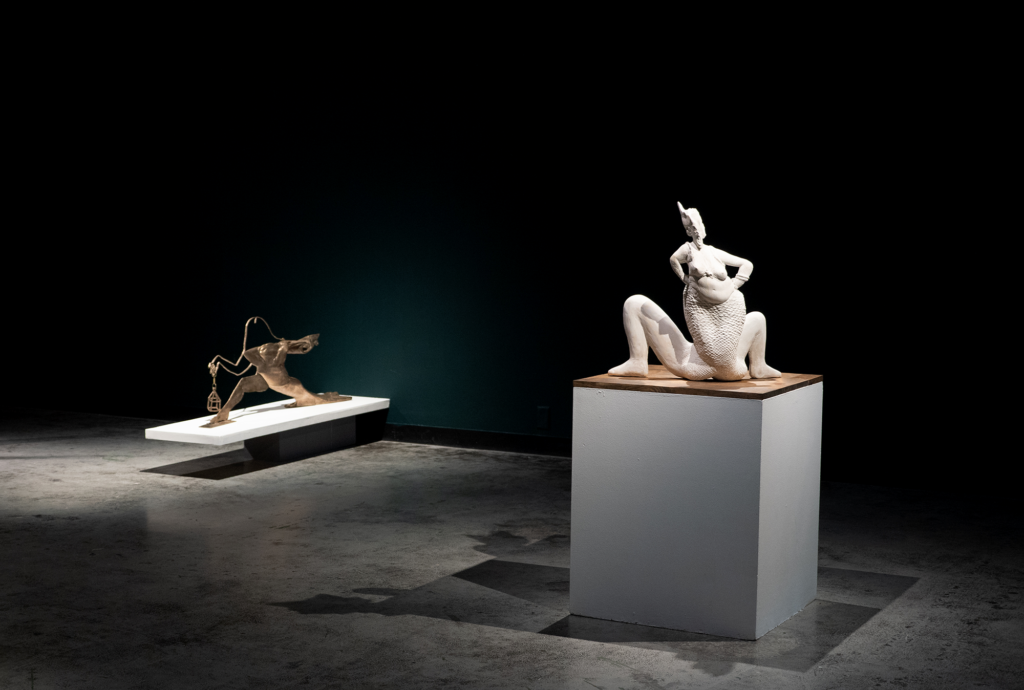 Two haunting sculptures by Shana Hoehn feature in a sparse, darkly lit gallery