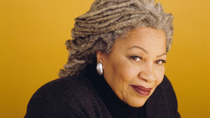 A portrait of Toni Morrison wearing a black turtleneck and set against a mustard-yellow background; she smiles slightly at the camera.
