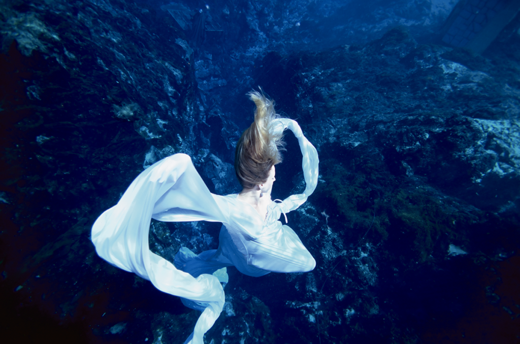 A dreamy underwater photo in which a blonde women wrapped in white sinks/floats surrounded by the immersive blue of the ocean.