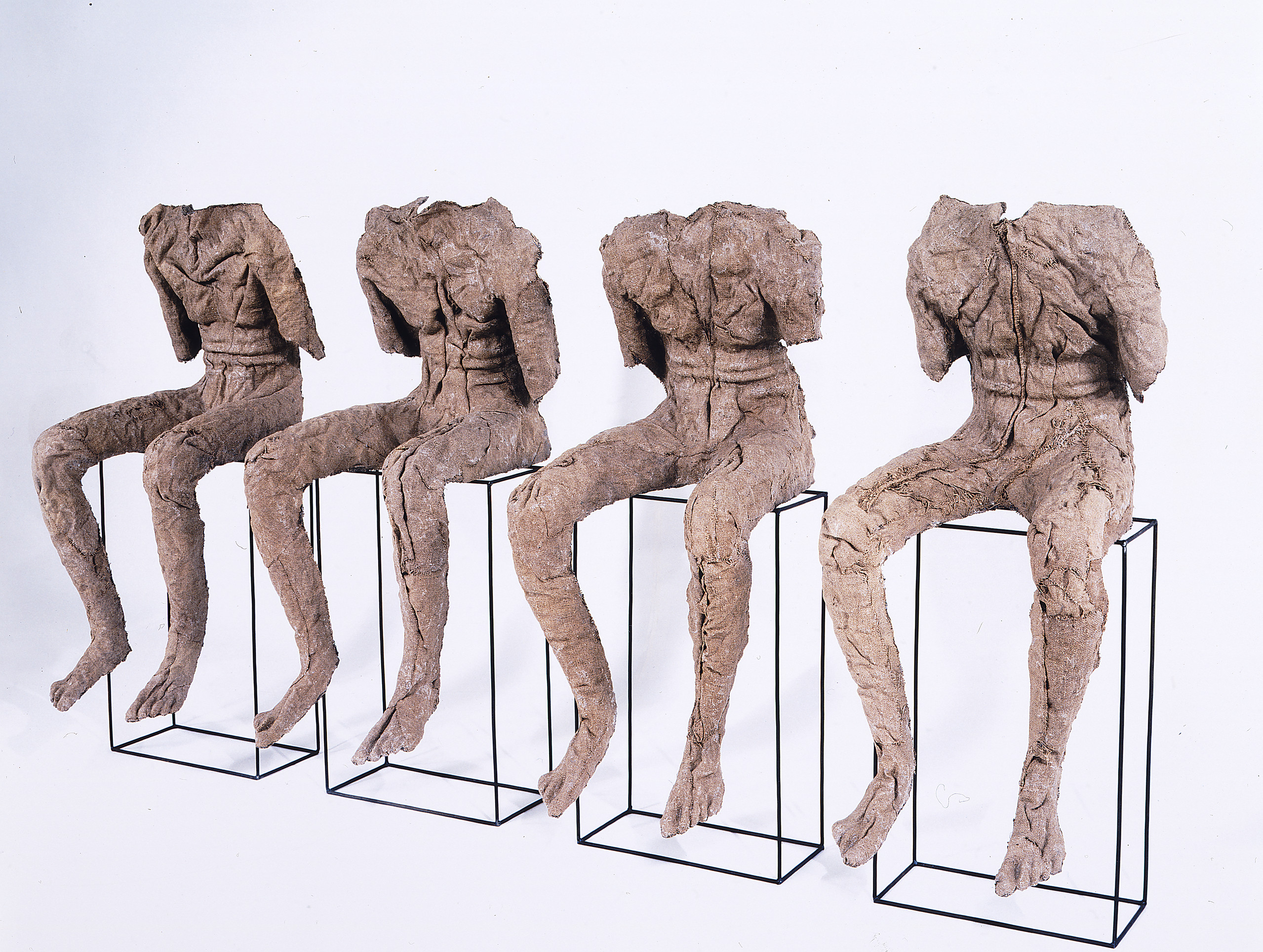 Four androgynous figures rendered in stiffened, brown burlap sit atop vertical, rectangular metal frames. They lack necks, heads, lower arms, and clothing, and their upper torsos slump slightly forward. The burlap's color and bumpy texture evoke bark and mummy wrappings.
