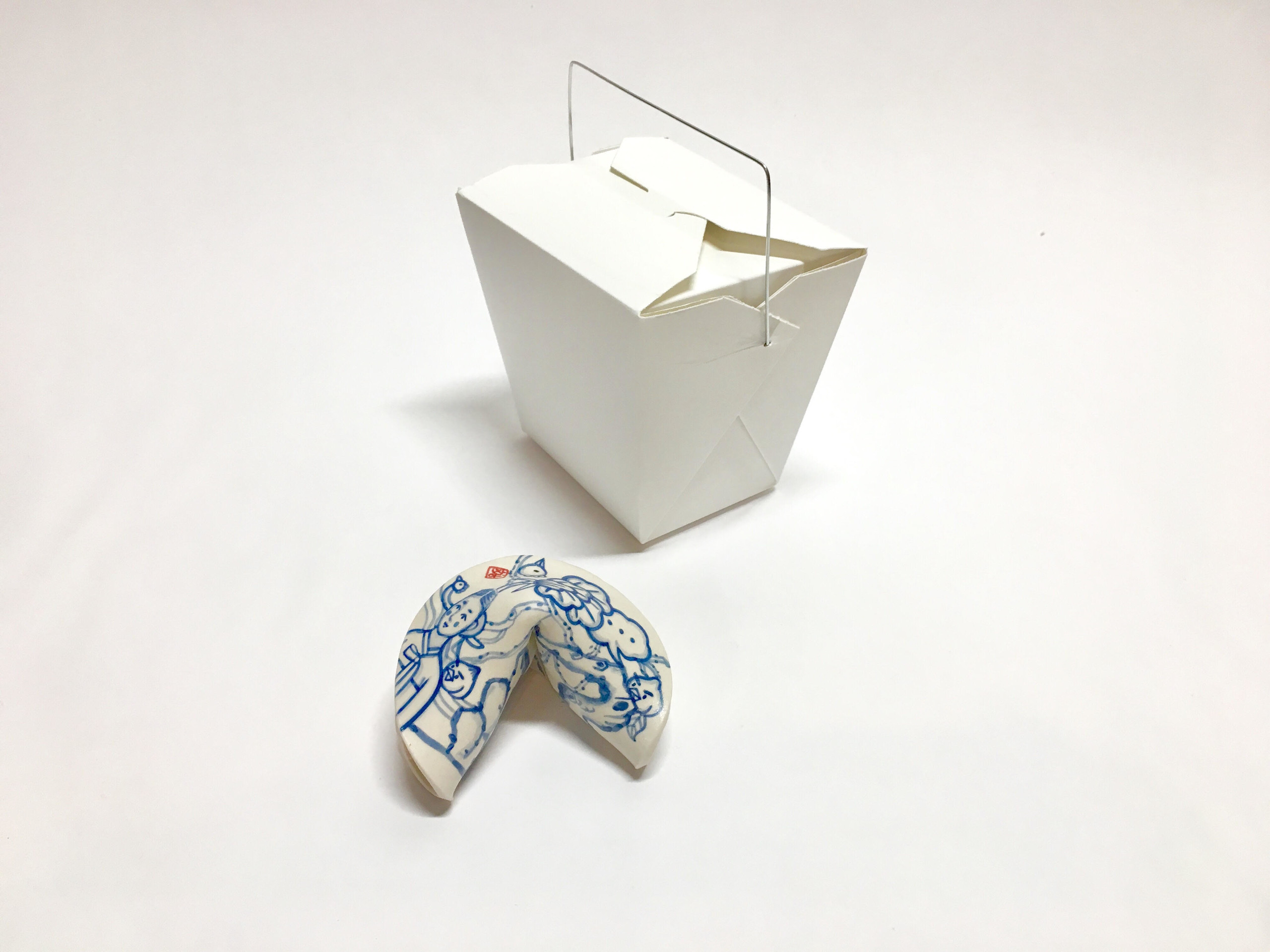 A small blue and white painted porcelain fortune cookie next to a white takeout box