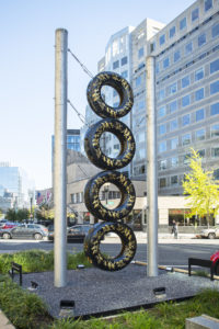 View of New York Avenue showing a tall, totem-like sculpture made of four stacked truck tires with gold leaf embellishments and supported by two steel poles.