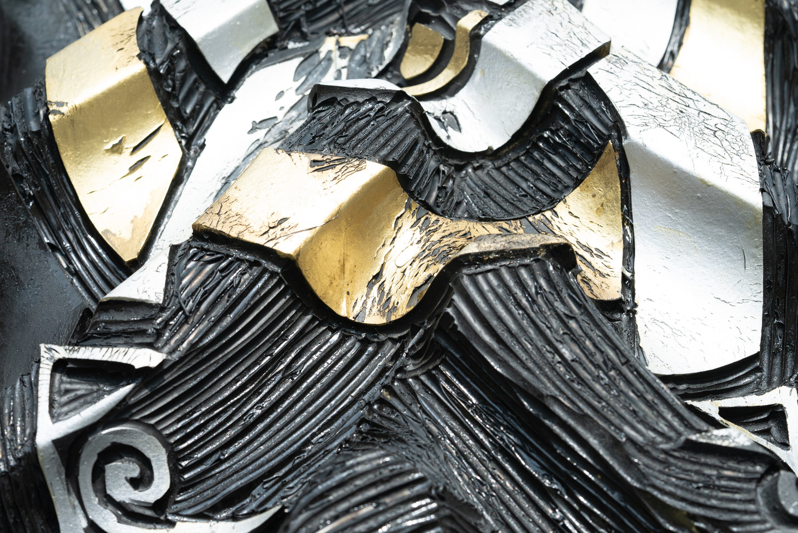 Closeup detail of an engraved tire with peeling ribbons of gold and silver leaf intertwined with varying directions of ribbed black lines.