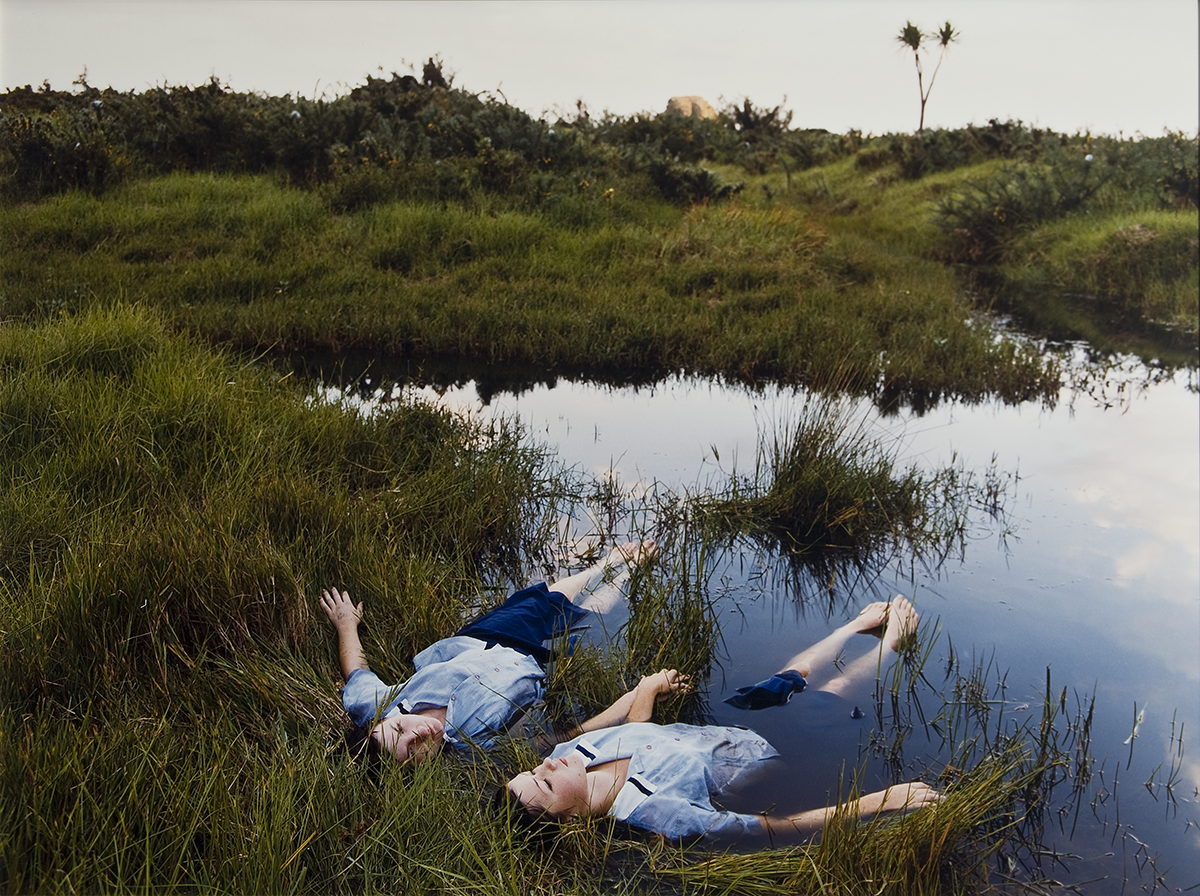 Two girls in matching blue school uniforms--dark blue skirt, light blue oxford shirt--lay in grassy marshland with the lower half of their bodies somewhat submerged.
