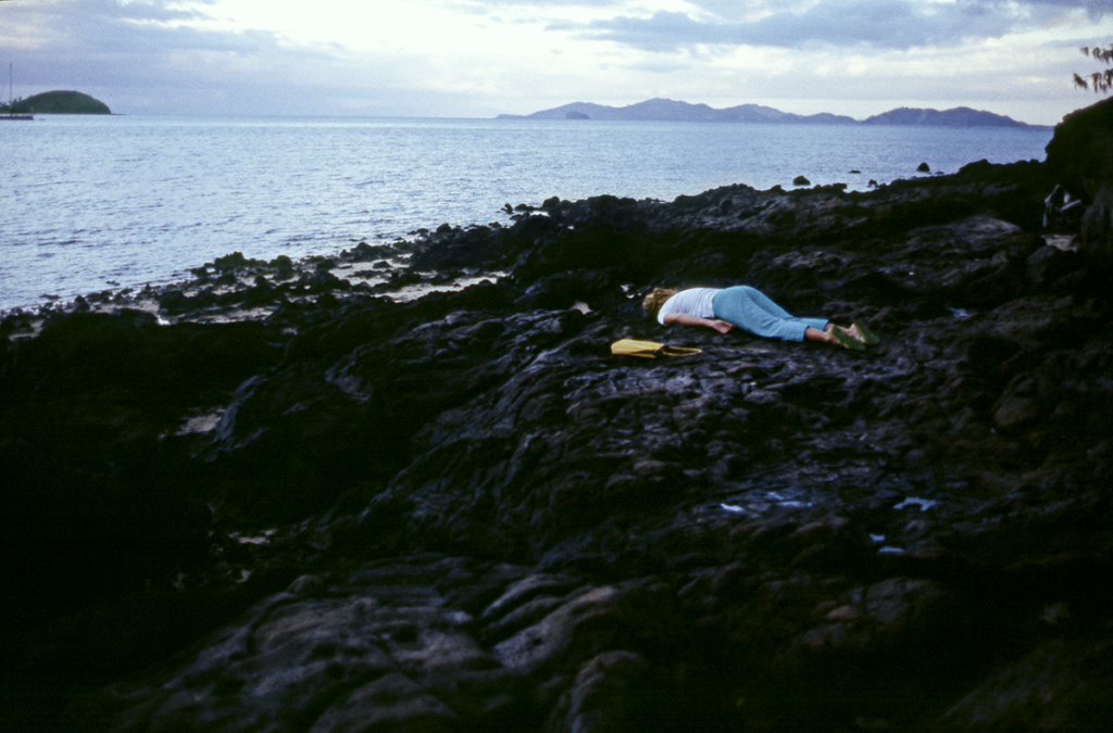A woman lies face down on a rocky coast with a yellow purse next to her. In the distance, on the sea's horizon, are mountains.