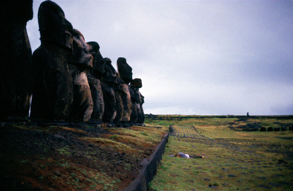 A woman lies face down in front of the towering Moai statues on Easter Island off the coast of Chile.