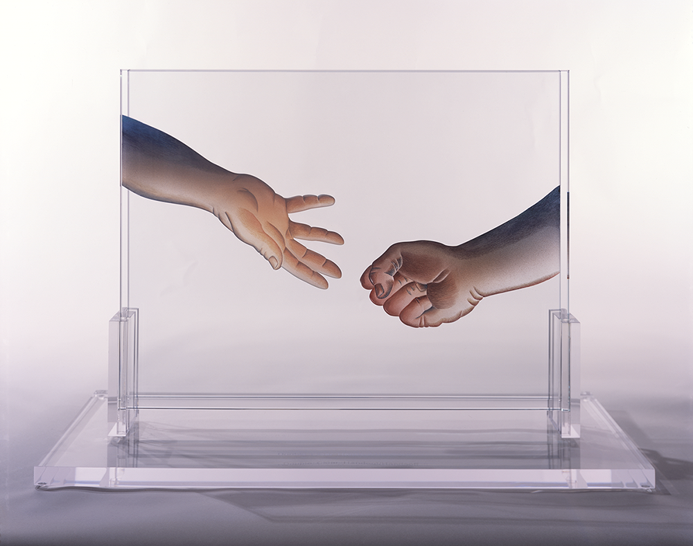 A clear glass block that has the image of two hands painted on it; one is clenched into a fist, the other is open and reaching toward the fist.