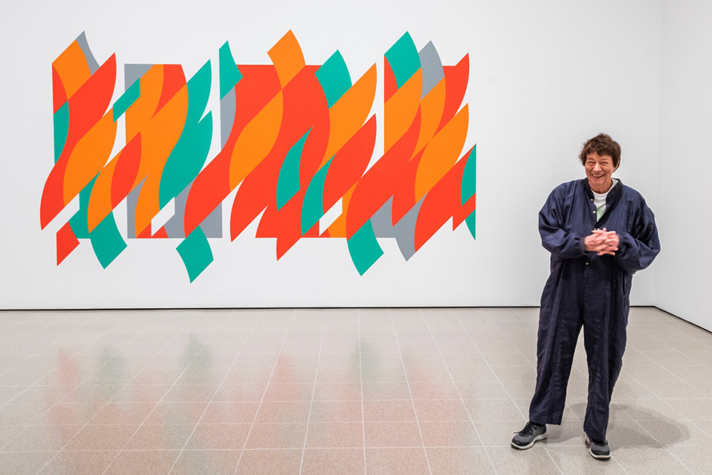 Artist Bridget Riley stands smiling, in a navy jumpsuit, in front of one of her vibrant abstract works.