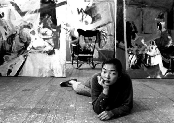Artist Berenice Bing lays on the wooden floor of her studio in the late 1950s, resting her head in her hands; in the background some of her paintings are visible, as well as a rocking chair