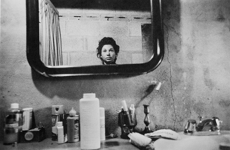 A black and white self-portrait of Abigail Heyman, her face visible in a bathroom mirror against a dirty concrete wall, the counter littered with various bottles and makeup.