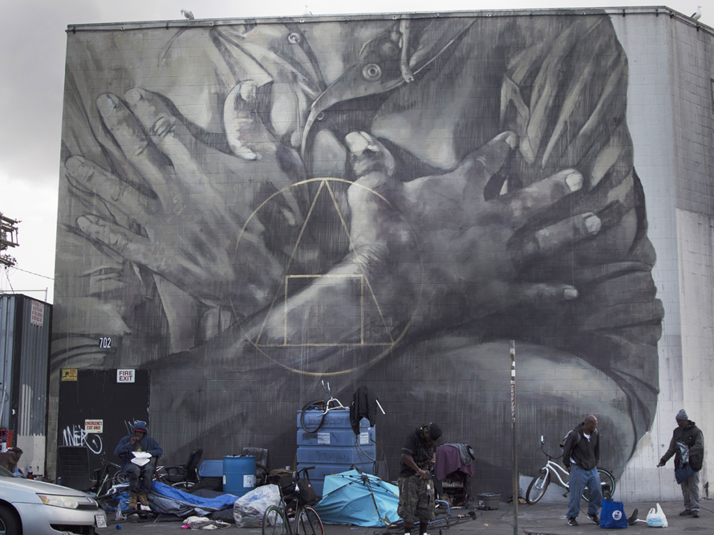 "A photograph of South African artist Faith XVVII's mural ""Salus Populi Suprema Lex Esto"" (2018) painted on a building on Skid Row in Los Angeles. It is a grayscale rendering of hands folded across a chest overlaid with geometric shapes."