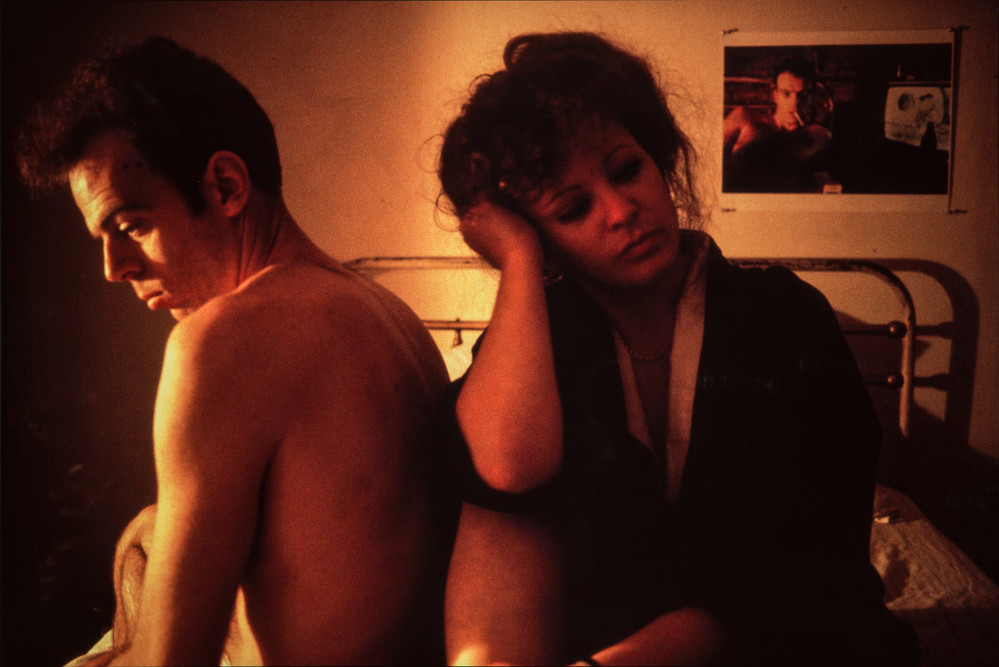 A man and woman sit next to each other on a bed. The man, topless, sits with his back to the woman. She sits leaning against him and looking away, her head resting on her hand and her elbow on her bent knee. A photo on the wall behind them appears to be of the same man.