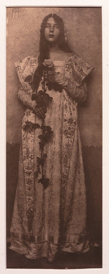 Narrow and vertical, this full-length photographic portrait depicts a light-skinned woman in sepia tones. Wearing a long, elaborately brocade dress, her long, dark hair cascading over one shoulder, she clasps an impressive long-stemmed rose in front of her with both hands.