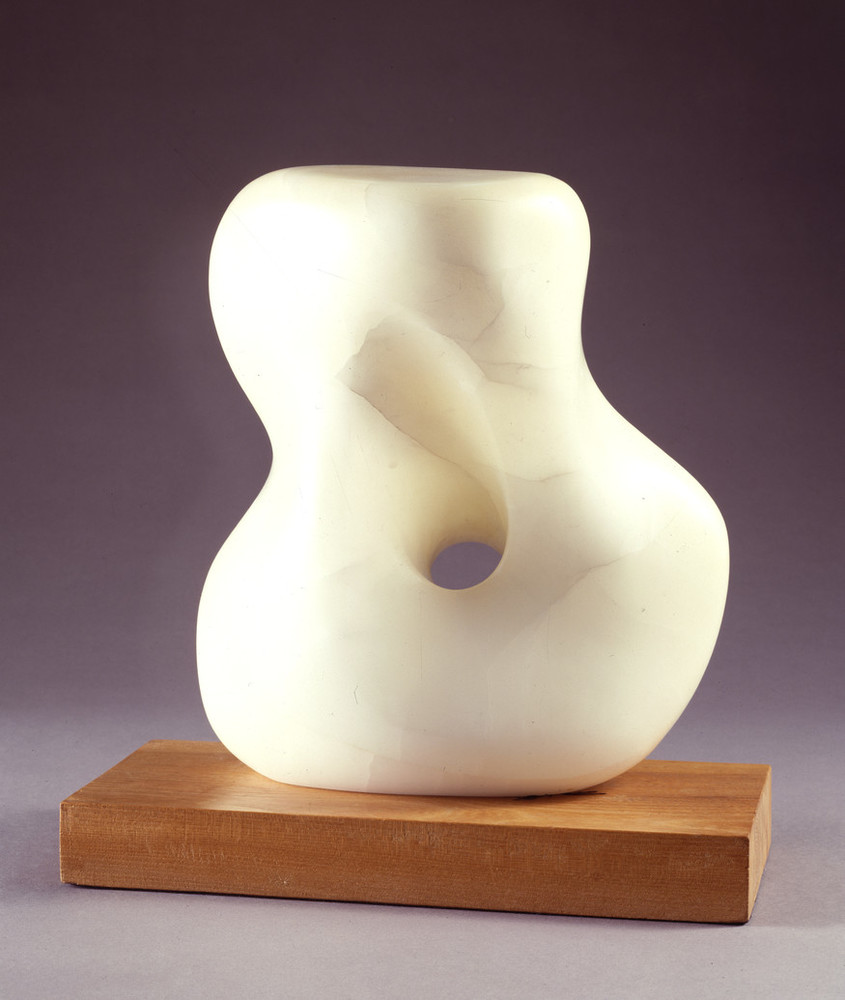 Abstract white stone sculpture, set on a light wood base, smooth and soft, it resembles a woman's twisting torso with a large, rounded hole through the middle.