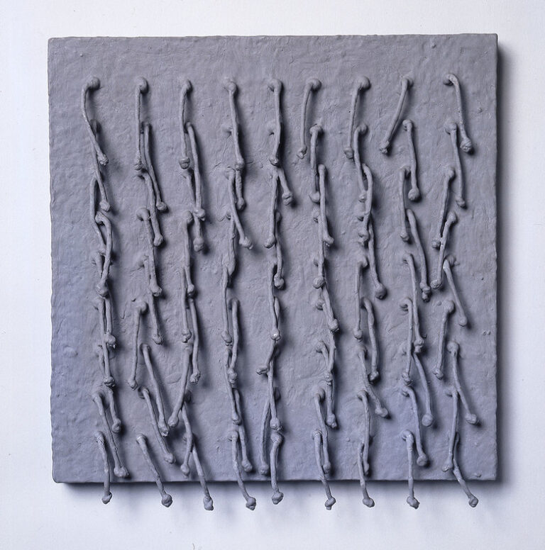 Short, knotted cords, arranged in a symmetrical 9-by-9 grid emerge from a square panel and hang down. Thick, matte-gray paint coats the entire piece, adding rough texture to the panel and stiffening the cords into positions that cast irregular shadows across the work's surface.