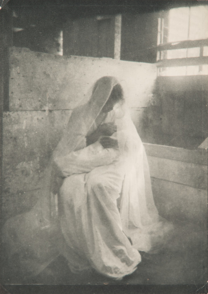 Ethereal photograph of a women wearing a long white dress and gossamer veil, sitting in a stable, holding a swaddled infant. Dramatically illuminated by a shaft of light streaming in, she gazes down at the child cradled in her arms.